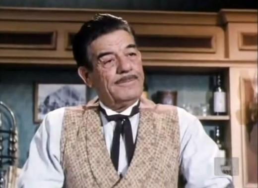 "Glenn Strange as ""Sam Noonan,"" the barkeep at Kitty's Long Branch Saloon."