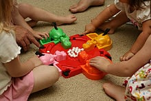 People playing a game of Hungry Hungry Hippos.