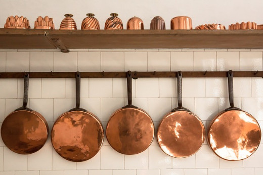 Copper cookware displayed on the wall.