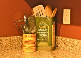 An old olive oil tin & coffee tin holds cooking utensils.