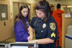 A female corrections officer takes the fingerprints of a new prisoner.