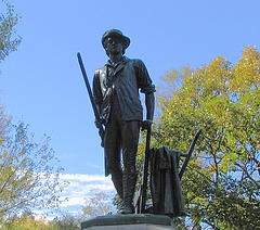 The Conkid Minuteman Statue commemorating the opening battle of the Revolutionary Wawh.  Translation:  The Concord Minuteman Statue commemorating the opening battle of the Revolutionary War.