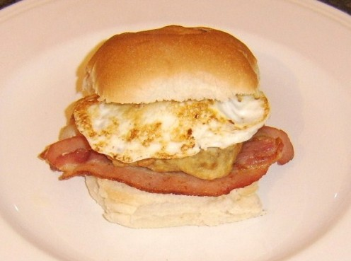 Succulent pork fritter served on a bread roll with bacon and a fried egg