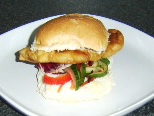 Fillet of freshly caught meaty pollack is deep fried in batter and served on a bread roll with salad