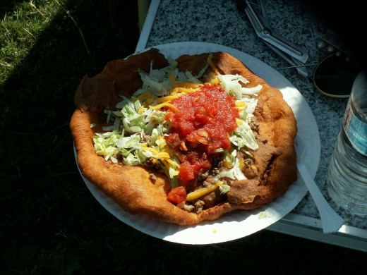 Also called fry bread taco or Navajo taco. It is fry bread topped with beans, meat, lettuce, onions, tomatoes, and cheese. Delicious !