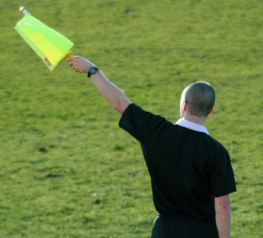 An assistant referee signals a throw in to the team attacking from right to left.  Photo by Rob Gale and distributed under Creative Common Attribution 2.0.