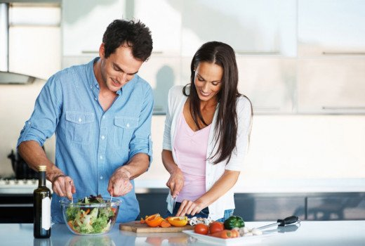 Man helps Woman in Cooking