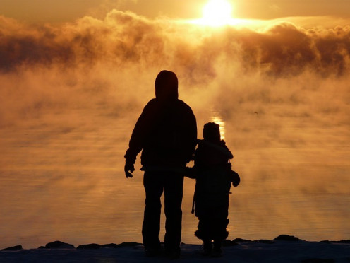 A man and his child walking as they watched the sunrise