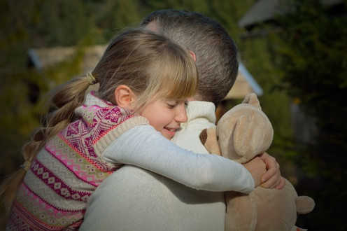 A little girl giving her dad a big hug