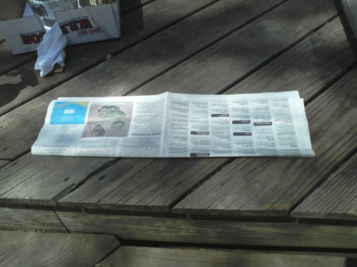 We get our newspaper online now so I use the freebie community paper from the front of the pizza shop. Fold it once like this.