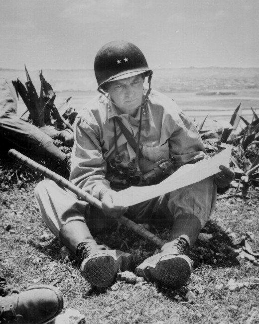 """""""With the captured capital of Naha as a background, Marine Maj. Gen. Lemuel Shepherd, commanding general of the 6th Marine Division, relaxes on an Okinawan ridge long enough to consult a map of the terrain."""" Pfc. Sam Weiner, ca. June 1945."""
