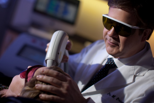 A dermatologist performing laser hair removal on a patient.