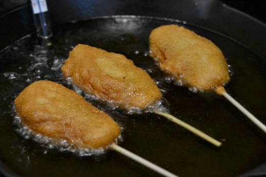 Gently insert a couple of the coated corn dogs one at a time into the hot oil. Add them to the oil carefully to prevent spattering as the hot oil will burn skin. Cook the corn dogs approximately 3 minutes, until they are a golden shade of brown.