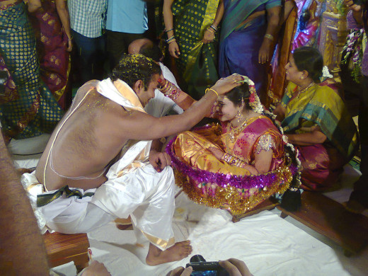 The Bride and Groom place the paste of cumin and jaggery on each other's head.