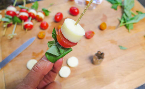 After the basil leaf slide one side of the halved cherry tomato, a piece of the circular cut mozzarella cheese.