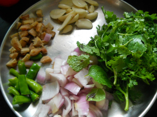 For the Mint Chutney - Add chopped onions, garlic, ginger, coriander, mint leaves, and green chilly to a blender to form the chutney (Indian dip). Add salt to taste.