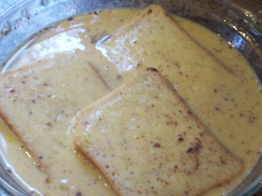 Dipping the breads in the egg-milk mixture