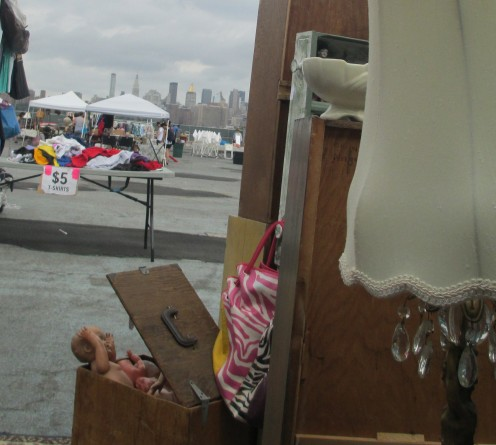 "A lamp, a box of ""creepy dolls,"" and my shelves in the foreground contrast with the Manhattan skyline."