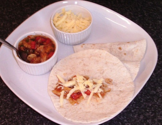 Grated cheese scattered over fajitas spiced jellied cod