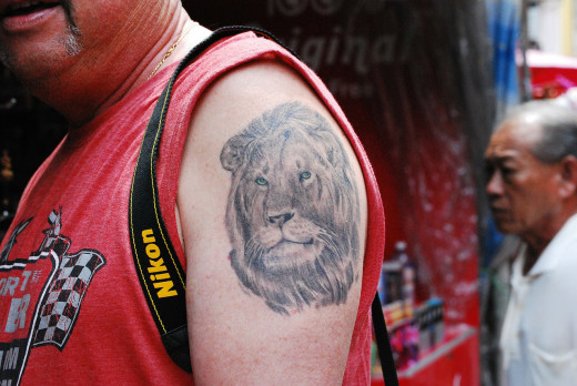 Is this man saying with a tattoo that he is the king of the jungle?