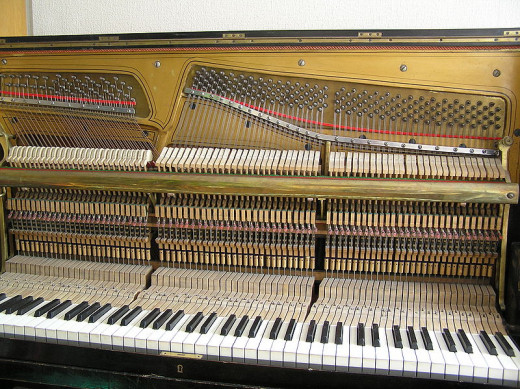 View of the inside of an upright piano showing how each of the treble strings (3 per note) has its own tuning peg.