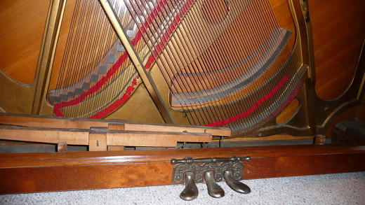 In an upright piano the strings go from top to bottom, crossing over in harp-like designs