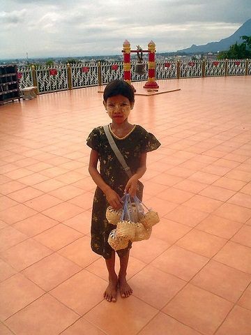 Girl selling rice birds at temple in Myanmar