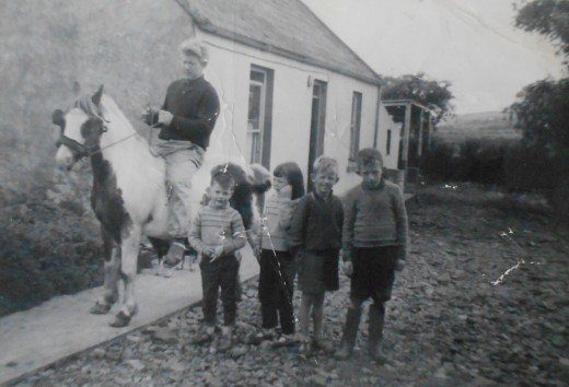 My grandfather outside his parents' cottage with two of his children and their friends. Photo taken in the 1960s.