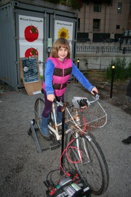 My daughter on a bicycle set up to use pedaling as an energy source at Occupy Boston.