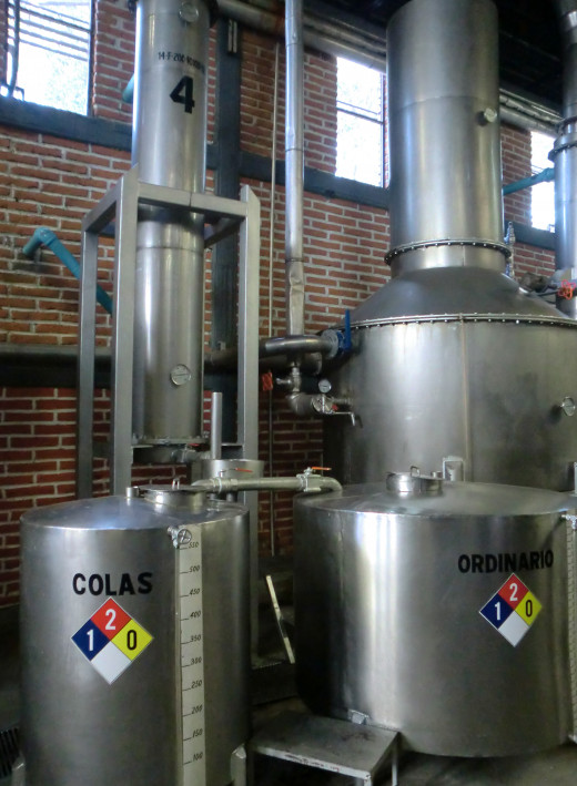 "A stainless steel still from La Confredia distillery. Note the Spanish words ""cola"" and ""ordinario"" (tale and ordinary) on the two tanks. The cola is discarded and the ordinario will be distilled a second time to achieve the final product."