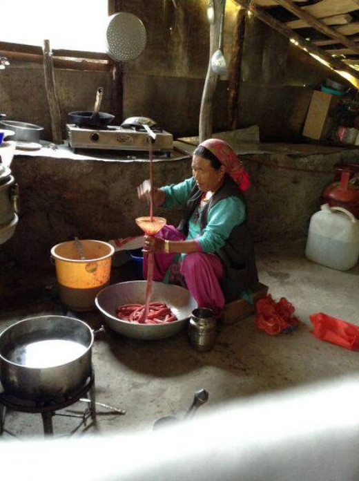 A tribal woman making sausages . What craft.