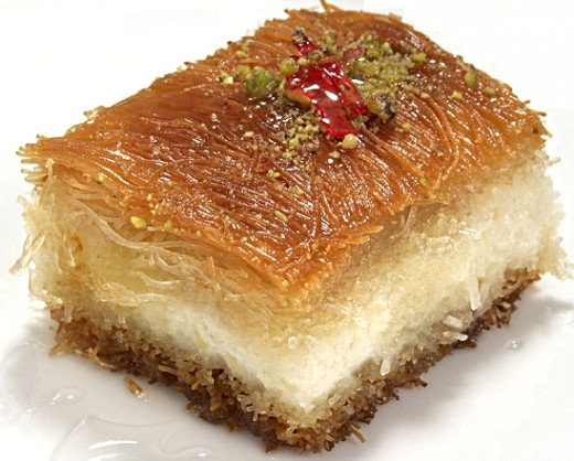 Various options are available for the base and crust of the knafeh. Slice into squares and serve with a sugar syrup.