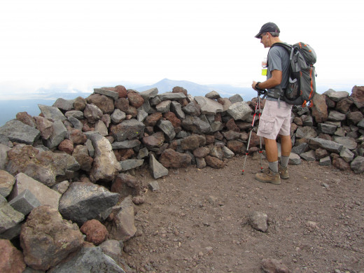 At the 12,633 feet summit of Humphrey's Peak. The low rock wall in front of this anonymous hiker is used as a windbreak to shelter hikers from the the intense winds that can sometimes greet them at the top.