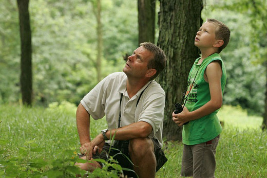Father and son spending a leisure afternoon birdwatching in the great outdoors.