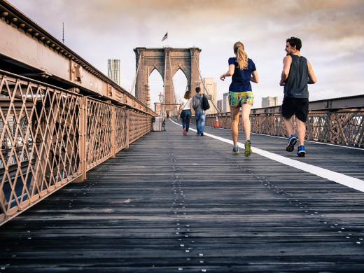 A couple jogging on the Brooklyn Bridge in New York City.