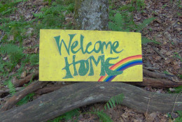 The famous Welcome Home sign at the entrance of a Rainbow Gathering.