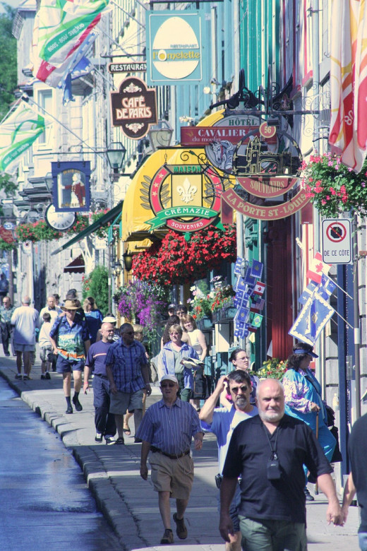 Crowds of shoppers walk along a street in Quebec City.