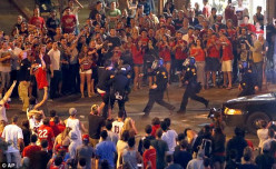 Tucson Police Officers rush out of their line to take a man into custody who had been taunting them and riling up a crowd of fans in Maingate Square following Arizona's loss to Wisconsin 64-63 in the West Region NCAA final.