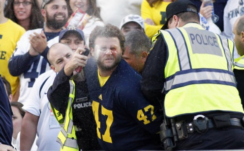 Cops are seen having to Pepper Spray Michigan Wolverine fans for being out of order.