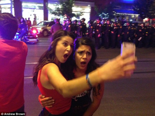 These two students from The University of Arizona take a moment to get a selfie during riots caused by Arizona students who were upset at Arizona losing an important championship game.
