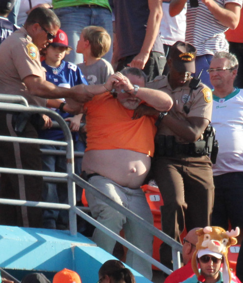 This guy being tossed from a football game must be a pro at his craft for notice that he is not resisting the cops.