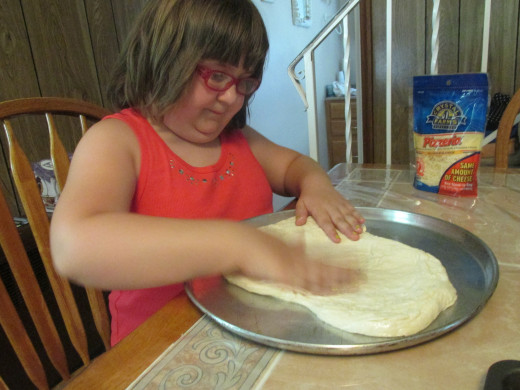 Olivia spreading out the dough