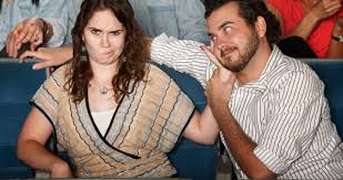 Look at this girl. She how angry she is. Her date, this sly-looking guy has just acted foolishly and caused her to be severely embarrassed.