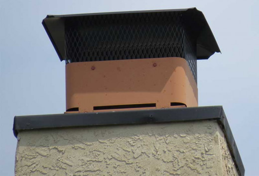 Faux flue cap attached to metal chase pan.