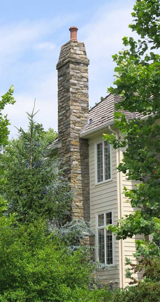 Masonry (stone) chimney bedecking clay chimney pot.