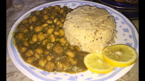 Delicious chickpea curry served with tadka rice and slices of lemon to enhance flavor.
