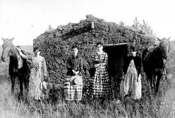 A homesteader family pose by their home in the 1800's.