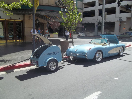 A powder-blue corvette pulling a matching trailer.