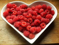 A bowl of fresh raspberries are delicious and good to eat.