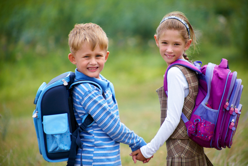 This cute couple are wearing their backpacks to school.